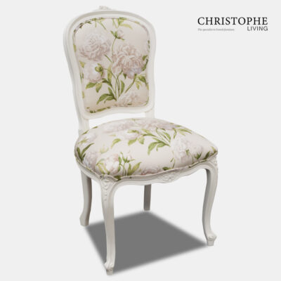 White French provincial dining chair with cream and green floral fabric and shield back shaped seat.