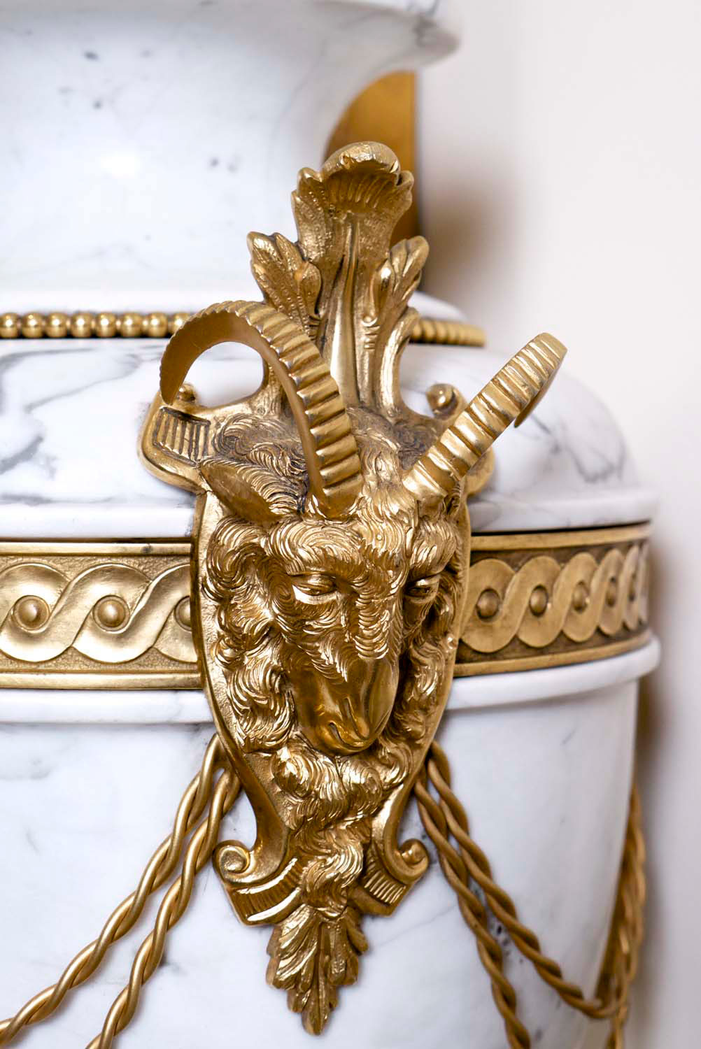 4 Gilding detail on french décor urn with deocrative motif positoned in hall way