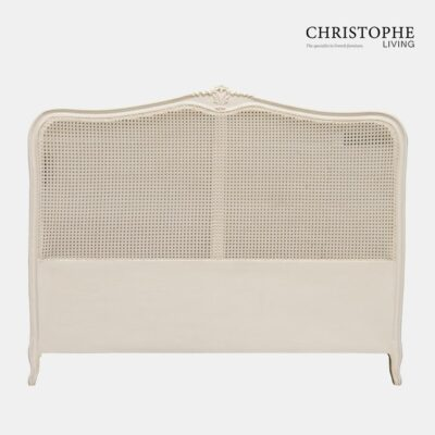 A painted French style bedhead upholstered with cane and finished in antique white with carving details
