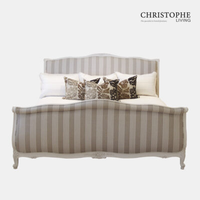 Linen upholstered bed in French style with sleigh bed design and linen cushion and decorative cushions with floral motif