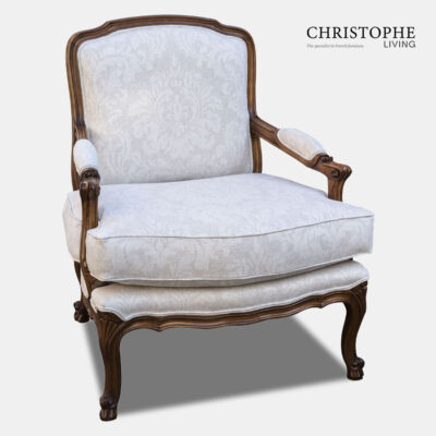 Timber armchair in the French provincial style with a hand applied timber finish. Upholstered in a light linen damask fabric with upholstered arm rests.