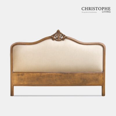 Ornate carved bedhead in French style in timber finish with linen upholstery