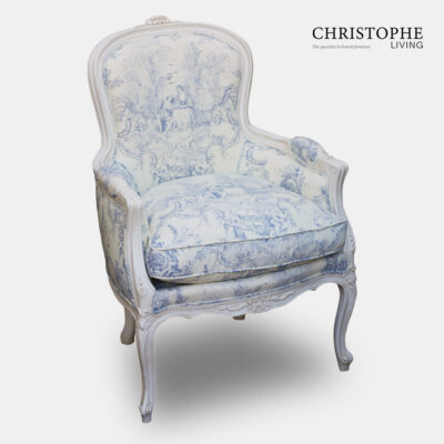 French bedroom chair in blue and white jovial fabric with cushion and curved legs painted white.