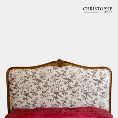 A French provincial bedhead upholstered in grey and cream bird toile linen fabric with timber in walnut finish