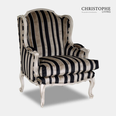 Armchair carved French provincial style with painted finish and antique patina. Upholstered in a velvet stripe with black and gold tone.